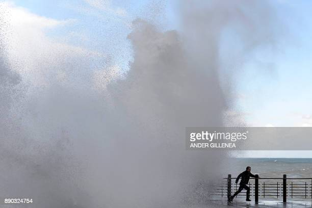 TOPSHOT A man flees giant waves crashing on a seaside promenade in the northern Spanish Basque city of San Sebastian on December 11 2017 Alerts have...