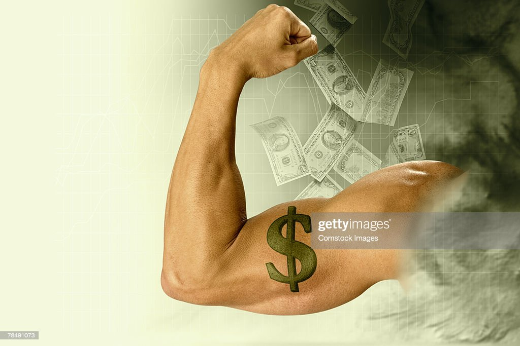 Man flexing a muscular arm with dollar sign tattoo surrounded by falling money : Stock Photo