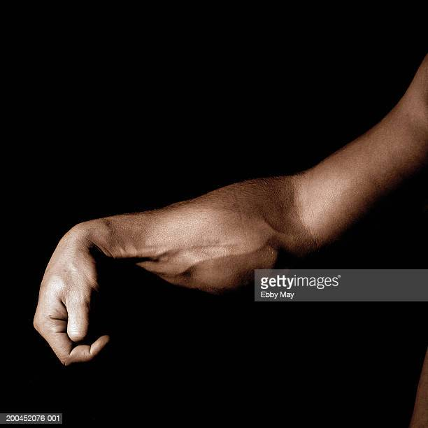 man flexing muscles of forearm, close-up (toned b&w) - human arm stock pictures, royalty-free photos & images