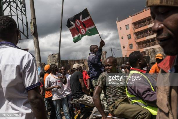 A man flies a Kenyan through the street in the Kawangware slum after a visit from presidential candidate Raila Odinga on October 29 2017 in Nairobi...