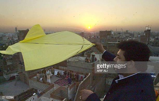 A man flies a kite at sunset after a daylong kite flying festival locally known as Basant in Pakistan's eastern city of Lahore on February 9 as...