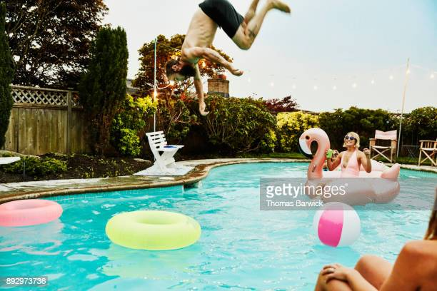 Man flipping into backyard pool while friends watch during party on summer evening
