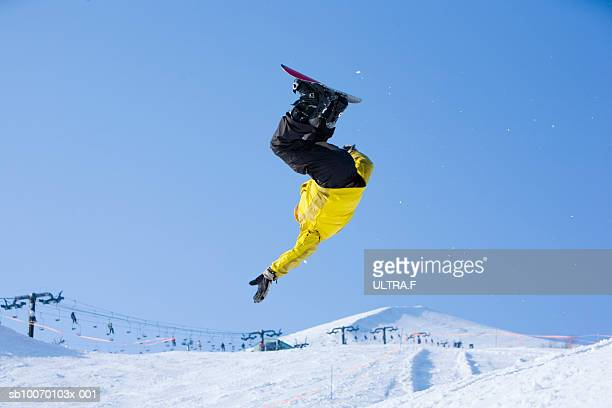 Man flipping on snowboard