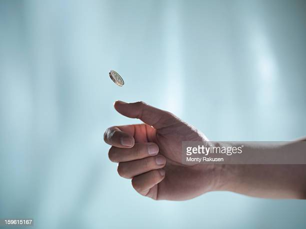 man flipping one pound coin, pounds sterling - lanciare foto e immagini stock