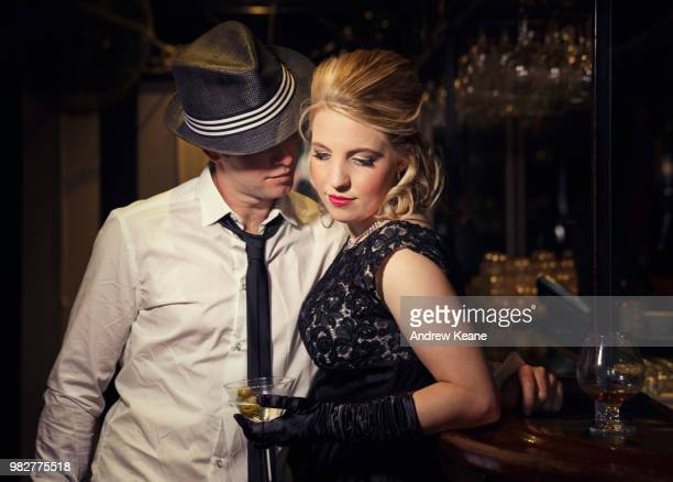 man flirting with elegant woman in bar - fedora stock pictures, royalty-free photos & images