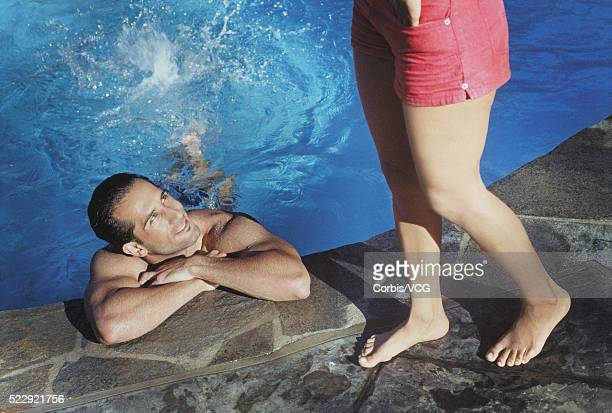 man flirting with woman by the pool - vcg stock pictures, royalty-free photos & images