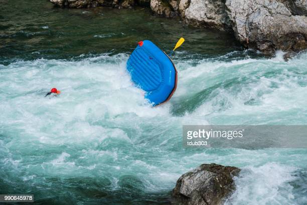 Man schwebt in einem Fluss nach seinem Floß während der Wildwasser-Raften umgedreht