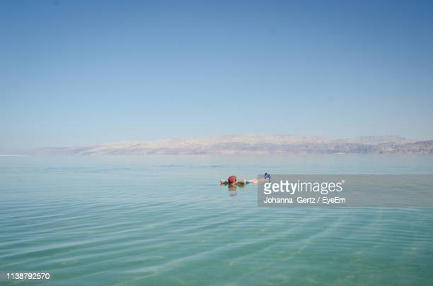 man floating in dead sea against clear blue sky - dead sea stock pictures, royalty-free photos & images