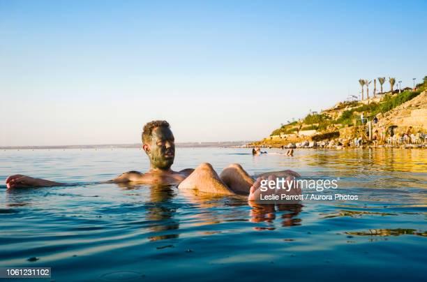 man floating in dead sea, madaba governorate, jordan - mar muerto fotografías e imágenes de stock