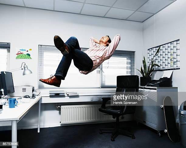 man floating in his office. - in de lucht zwevend stockfoto's en -beelden