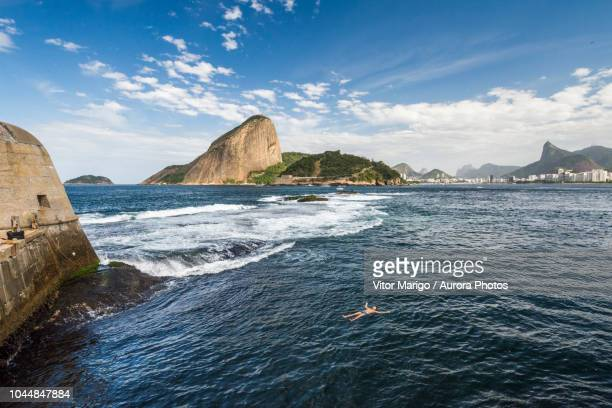 man floating in laje fort in guanabara bay, rio de janeiro, brazil - laje stock pictures, royalty-free photos & images