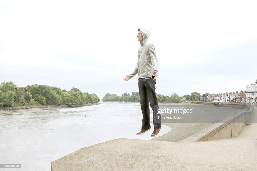 A Man Floating In Mid Air Next To River Stock Photo