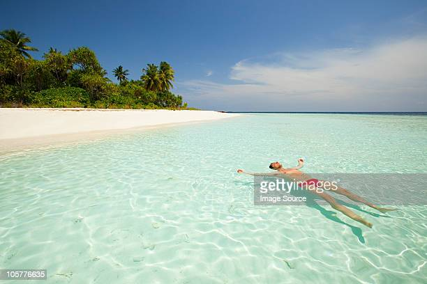Man floating in sea, Baughagello Island, South Huvadhu Atoll, Maldives