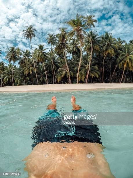 man floating in sea under palm trees - asian six pack stock photos and pictures