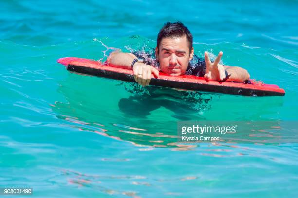 Man floating on a bodyboard at the beach