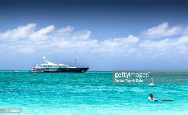 CONTENT] Man floating on inflatable float off Grace Bay beach with private yacht in background