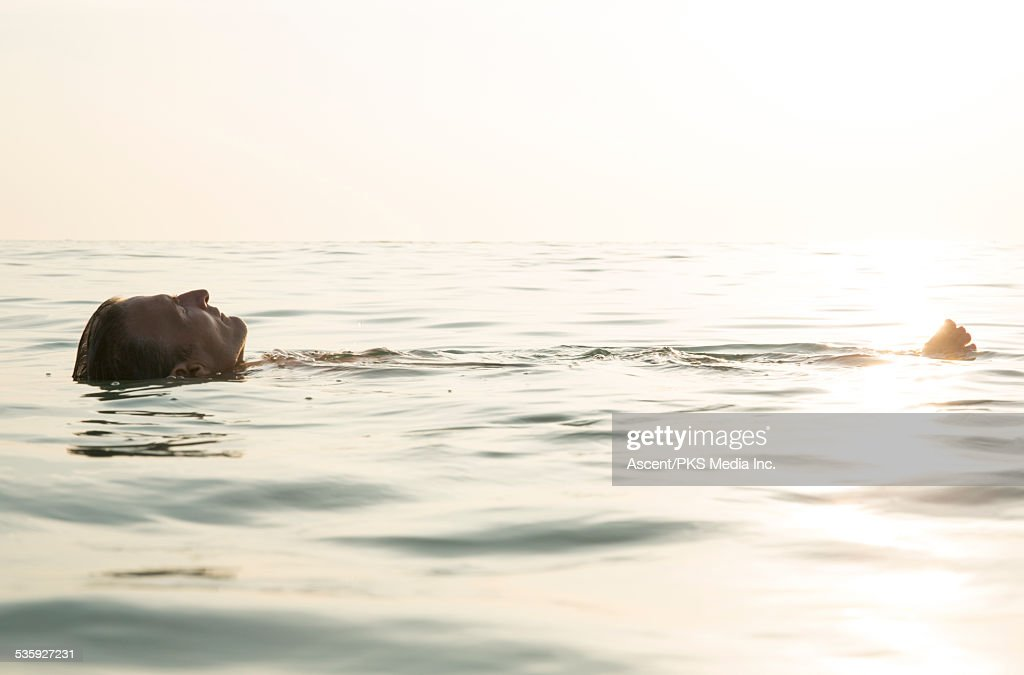 Man floats in sea, in deep relaxation : Stock Photo