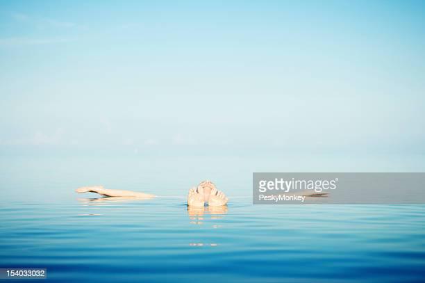 Homme flotte dans les eaux bleues paisibles