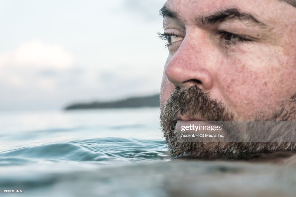 Man floats in tranquil sea, evening light : Stock Photo