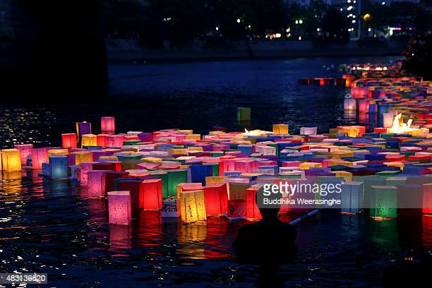 A man floats peace messages written on paper lanterns along the river during the 70th anniversary activities commemorating the atomic bombing of...