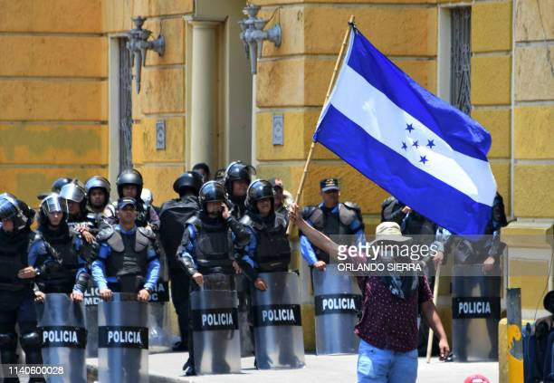 TOPSHOT A man flutters a Honduran national flag in front of a line of riot police during a May Day demonstration in Tegucigalpa on May 1 2019