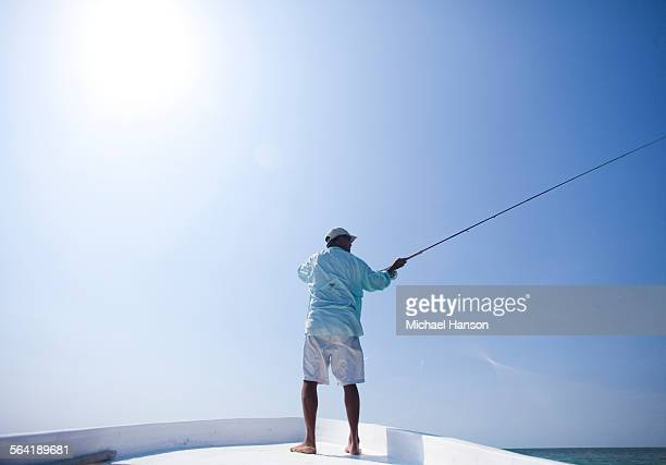 a man fly fishes in the clear waters off the coast of belize. - belize stock pictures, royalty-free photos & images
