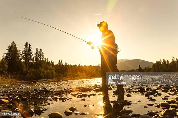 Man fly fishing at sunset or sunrise, Canada
