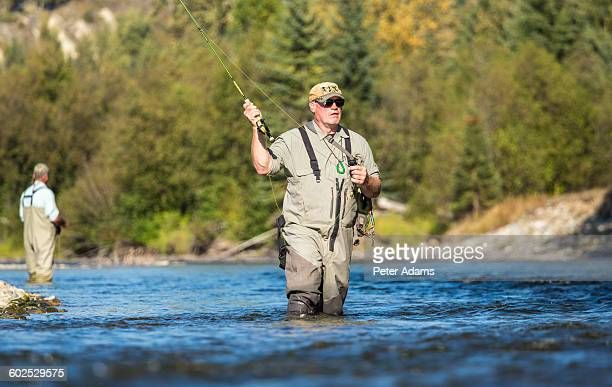 Man fly fishing, casting in river British Columbia