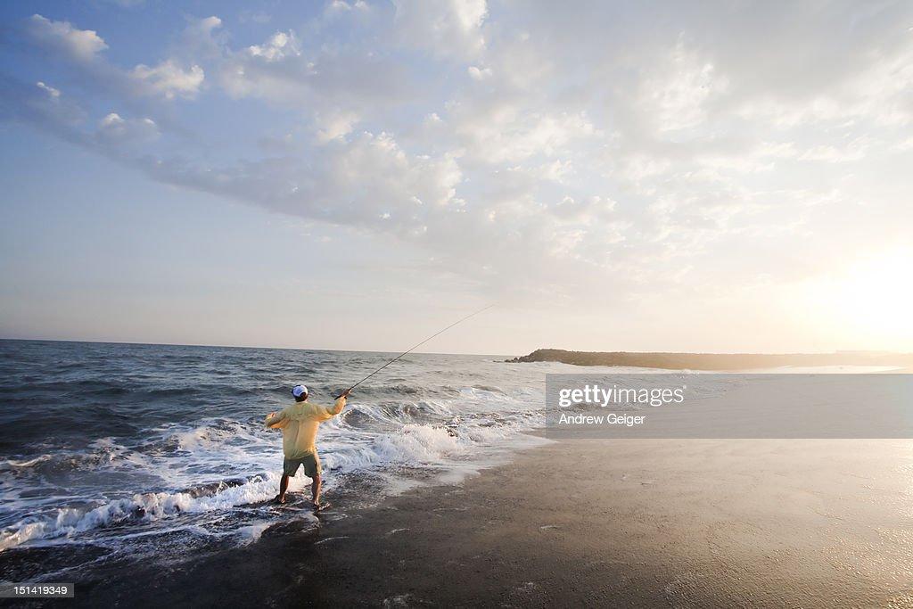 Man fly fishing in heavy surf. : Stock Photo