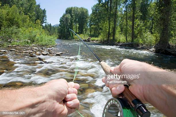 man fly fishing in river - personal perspective stock pictures, royalty-free photos & images