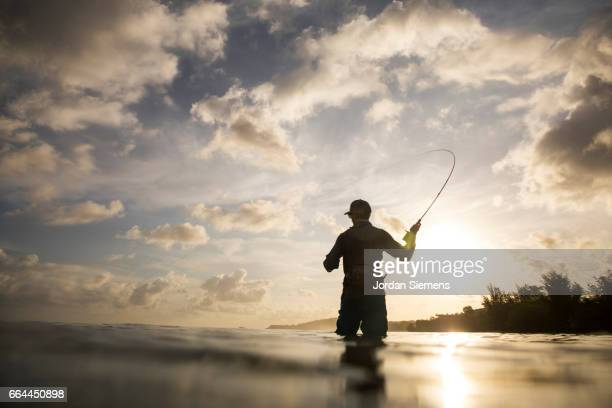 a man fly fishing in the ocean. - hobbies stock pictures, royalty-free photos & images