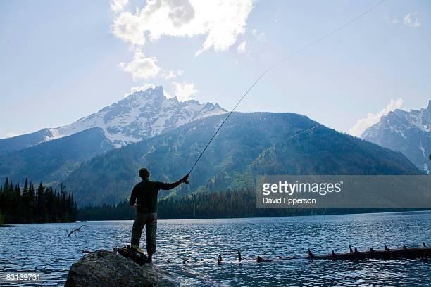 man fly fishing on Jenny Lake in Wyoming
