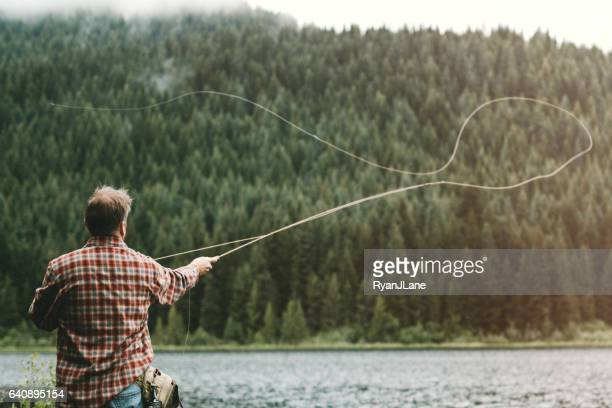 man fly fishing - fly casting stock pictures, royalty-free photos & images