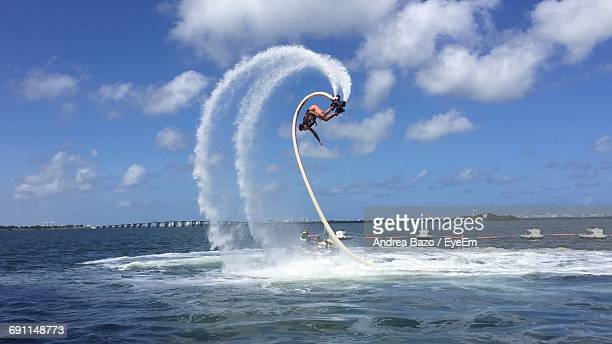 Man Flyboarding Over Sea Against Sky