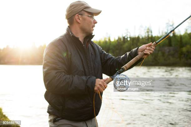 man fly-fishing in river - fishing industry stock pictures, royalty-free photos & images