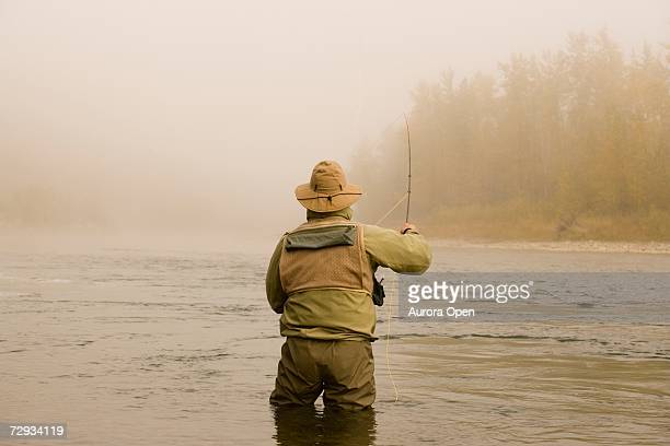 a man fly-fishing on elk river, bc, canada. - remote location stock pictures, royalty-free photos & images