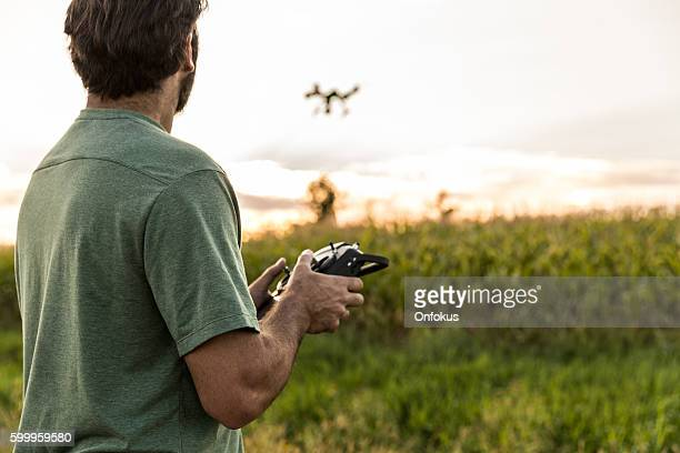 man flying a drone at sunset - drone photos et images de collection