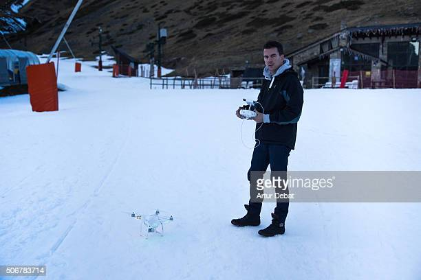 Man flying a drone in the snowy pyrenees with remote control attached to the smartphone.