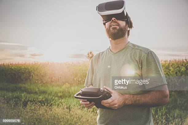 man flying a drone with virtual reality goggles headset - remote controlled stock photos and pictures