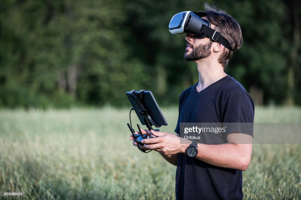 Man Flying a Drone with Virtual Reality Goggles Headset : Stock Photo
