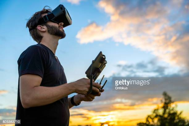 man flying a drone with virtual reality goggles headset - flying stock photos and pictures