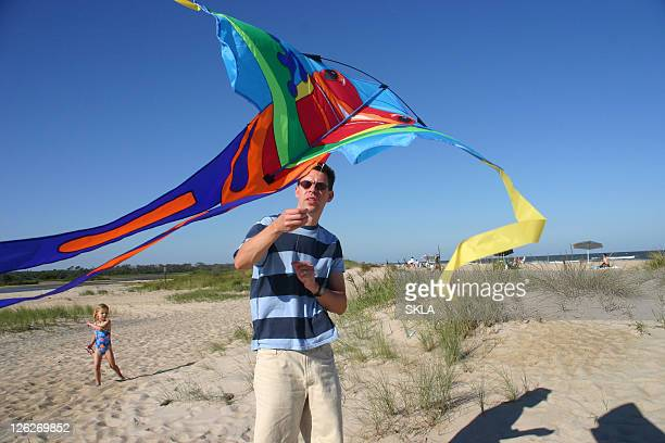 Man flying a kite with child watching in the background