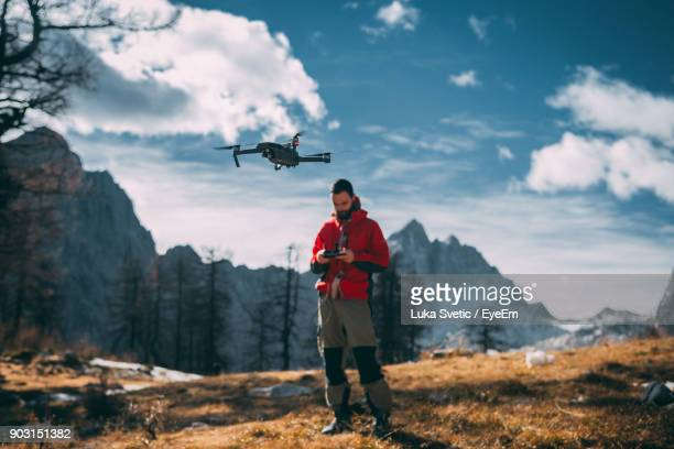 man flying drone against mountains - drone photos et images de collection