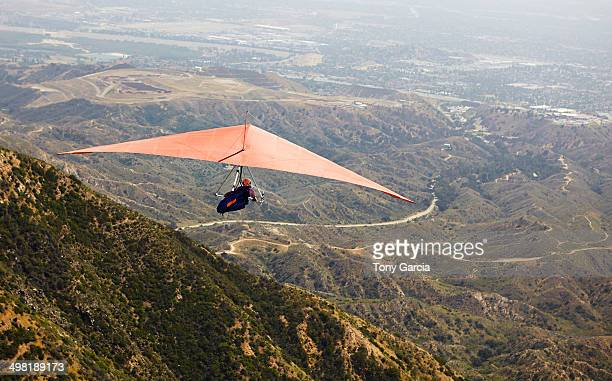 Man flying hang glider over valley
