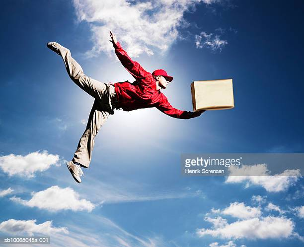 Man flying in sky with box in one hand, low angle view