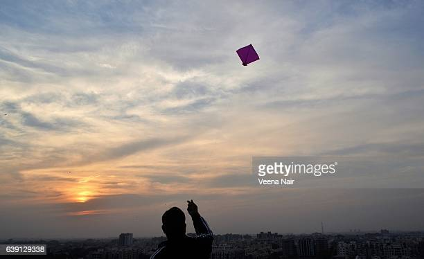 A man flying kite against a setting Sun-Uttarayan-Makar Sankranti-Gujarat