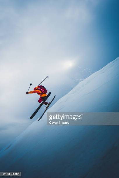 man flying off ski jump with sun and sky behind him - skiing stock pictures, royalty-free photos & images