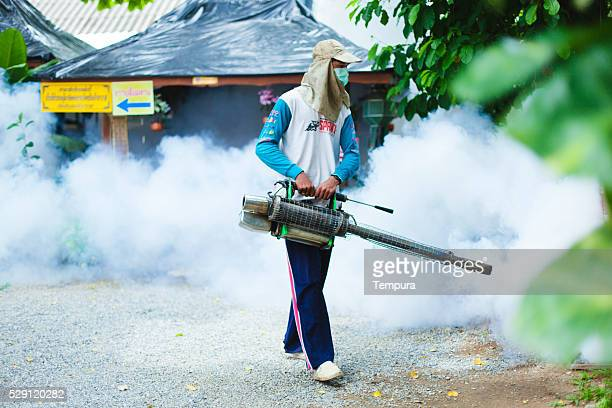 Man fogging mosquito spray in a public park