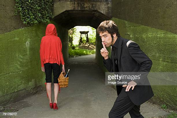 man following little red riding hood - stalker person stock photos and pictures
