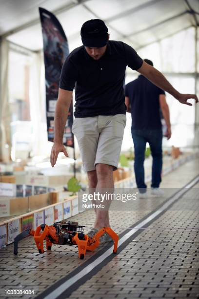 A man follows his creature along the track before the run A robots race took place in Toulouse Machines are either cars or walking robots They were...